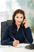 young office worker talking on landline phone in office