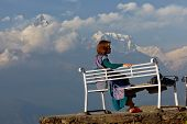 woman sitting on a bench on a background of mountains