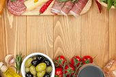 Red wine with cheese, olives, tomatoes, prosciutto, bread and spices. Over wooden table background. View from above with copy space