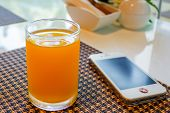 Glass Of Orange Juice With Mobile Phone.
