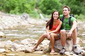 Hiking couple - hikers resting in Zion National Park. Young woman and man hiker sitting by river wat