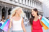 Shopping women happy holding shopping bags walking having fun laughing. Two beautiful young Asian woman and Caucasian woman girlfriends on travel vacation, Piazza San Marco Square, Venice, Italy.