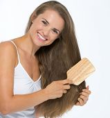 Smiling Young Woman Combing Hair