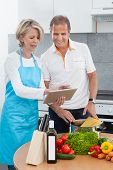 Mature Couple Using Tablet While Cooking
