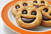 closeup of a plate with a pile of smiley biscuits