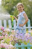 Watering, flower garden - beautiful girl watering roses with garden hose