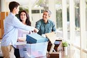 stock photo of 16 year old  - Parents Helping Teenage Son Pack For College - JPG