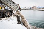 Truck Unloading Snow Into The River