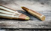 stock photo of bullet  - four rifle bullets on old wood desk - JPG