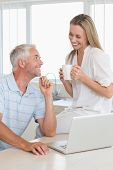 Cheerful couple using laptop together smiling at each other at home in the kitchen