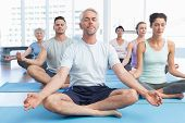 Sporty people in lotus pose with eyes closed at a bright fitness studio