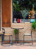 Cafe Chairs Against Brick Wall