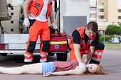 pic of paramedic  - Two paramedics applying first aid unconscious girl - JPG