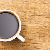 Black Coffee In White Ceramic Cup On Wooden Table - View From Top