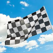 Checkered Flag Waving In The Wind With White Clouds
