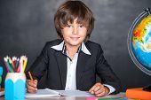 Cheerful school boy writing in notebook