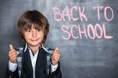 Close-up of little school boy with thumbs up near blackboard