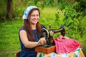 Happy woman with retro hand sewing machine