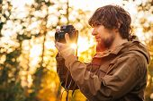 picture of swag  - Young Man with retro photo camera outdoor Lifestyle concept sunlight forest nature on background