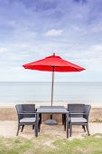 Outdoor Table Set, Beach Chairs And Red Umbrella With Beautiful Beach And Blue Sky Background.