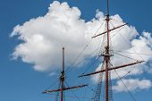 stock photo of brigantine  - Two mast sailing ship with sails raised on the background of clouds in Amsterdam - JPG