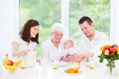 Young Family With A Little Baby Having Breakfast With Their Loving Grandmother