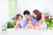 Happy Young Family enjoying Easter breakfast in a white sunny dining room