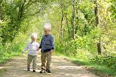 Young Children Holding Hands Taking A Walk In The Autumn Woods