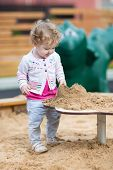 Cute Curly Baby Girl Playing With Sand On A Playground