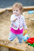 Cute Little Baby Girl Digging In Sand On A Playground