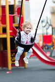 Happy Smiling Baby Girl Enjoying A Swing Ride On A Playground