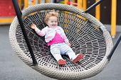 Happy Laughing Baby Girl Relaxing On A Swing