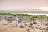 Beautiful little toddler girl watching the sunset at a beach