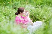 Young Pregnant Mother And Her Baby Daughter Relaxing In The Garden