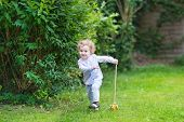 Adorable Baby Girl Playing In The Garden With A Wooden Toy
