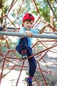 Little Boy In Cap Climb On Jungle Gym
