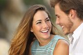 stock photo of casual woman  - Funny couple laughing with a white perfect smile and looking each other outdoors with unfocused background - JPG
