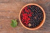 Sweet, Black And Red Currant And Green Leaves In Wooden Bowl.