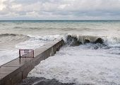 Storm waves roll on the breakwater.