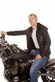 Man In Black Jacket Motorcycle On Hand On Handlebars Looking
