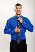 Man adjusts a tie