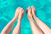 Two Pairs Of Female Legs In The Pool