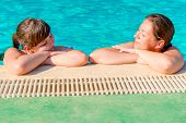 Two Women Relax At The Edge Of The Pool