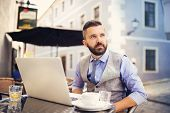 picture of internet-cafe  - Modern hipster businessman drinking espresso coffee in the city cafe during lunch time and working on laptop - JPG