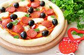 Pizza handmade with Salami, Mozzarella, Olives, Onion and Tomato Sauce
