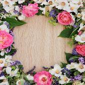 Summer flower border over light oak background.