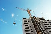 the construction of a multistory building using a crane.against the bright sky