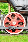 Red Iron Wheel Of Old Steam Locomotive. Outdoors Closeup.