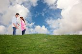 Couple arguing with each other against blue sky with white clouds