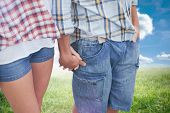 Couple in check shirts and denim holding hands against sunny landscape